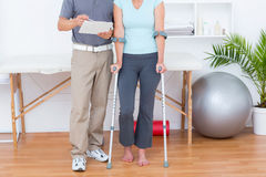 Woman using crutch and talking with her doctor Royalty Free Stock Image