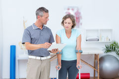 Woman using crutch and talking with her doctor Royalty Free Stock Photo