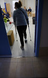 Woman using crutches entering to rehabilitation center Royalty Free Stock Photography