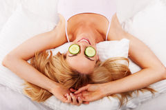 Woman using cucumber eyepads Royalty Free Stock Photo