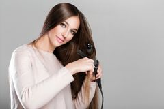 Woman using curling iron. Beautiful woman curling long hair using curling iron Stock Images
