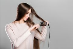 Woman using curling iron. Beautiful woman curling long hair using curling iron Royalty Free Stock Images