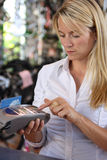 Woman using debit machine. Blond woman in white shirt using retail store's debit machine stock photography