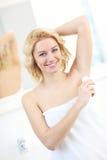 Woman using deodorant Stock Image