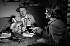 Woman using detective tablet at police department. Woman touching detective's tablet sitting at his office desk Stock Photo
