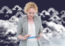 Woman using digital tablet. Against digitally generated cloud computing icons in  background Royalty Free Stock Photography