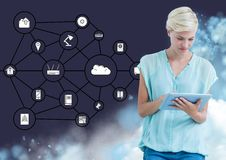 Woman using digital tablet against interface of connecting icons in the background. Digitally genrated image of woman using digital tablet against interface of stock image