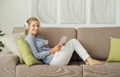 Woman using a digital tablet. Attractive woman relaxing at home in the living room, she is lying down on the sofa, wearing headphones and using a digital touch Royalty Free Stock Photo