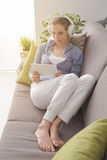 Woman using a digital tablet. Attractive woman relaxing at home in the living room, she is lying down on the sofa, wearing headphones and using a digital touch Royalty Free Stock Image