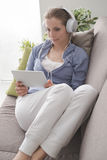 Woman using a digital tablet. Attractive woman relaxing at home in the living room, she is lying down on the sofa, wearing headphones and using a digital touch Royalty Free Stock Photos