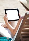 Woman using digital tablet on beach chair Stock Photos