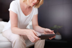 Woman using digital tablet on bed Royalty Free Stock Photo