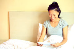 woman using digital tablet in bed at home Stock Images
