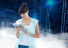 Woman using digital tablet with binary codes in background Royalty Free Stock Photography