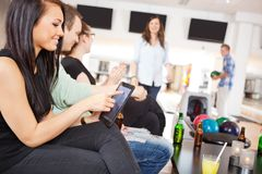 Woman Using Digital Tablet in Bowling Club Royalty Free Stock Images