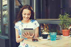 Woman using digital tablet at cafe Royalty Free Stock Photography