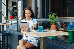 Woman using digital tablet at cafe Stock Images