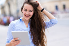 Woman using digital tablet on city street Royalty Free Stock Photo