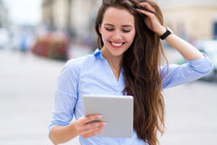 Woman using digital tablet on city street Royalty Free Stock Image