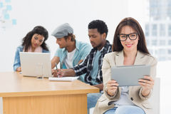 Woman using digital tablet with colleagues behind in office Royalty Free Stock Images