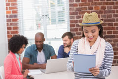 Woman using digital tablet with colleagues behind in office Stock Images