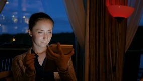 Woman using digital tablet computer device in cafe. Of cruise ship. Evening time, lowlight. Technology and entertainment concept stock video footage