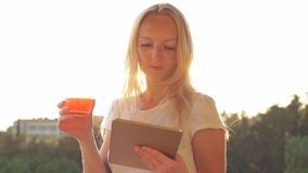 Woman using digital tablet and drinking juice on the sunset. Slow Motion.  stock video footage