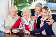 Woman Using Digital Tablet With Family At Nursing Stock Images