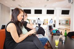Woman Using Digital Tablet With Friends Bowling in Stock Photo