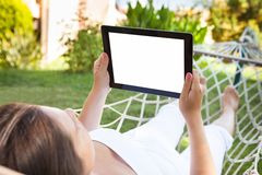 Woman using digital tablet in hammock at park Royalty Free Stock Photos