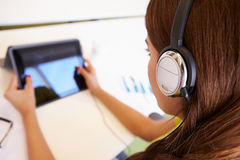 Woman Using Digital Tablet And Headphones In Design Studio Royalty Free Stock Images