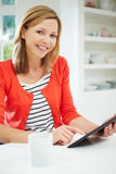 Woman Using Digital Tablet At Home In Kitchen Stock Photography