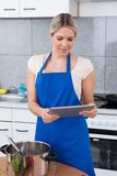 Woman Using Digital Tablet In Kitchen Royalty Free Stock Image
