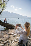 Woman using digital tablet by the lake Royalty Free Stock Image