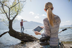 Woman using digital tablet by the lake Royalty Free Stock Images