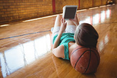 Woman using digital tablet while lying on floor Royalty Free Stock Photography
