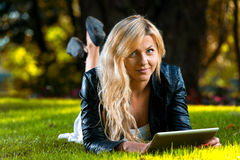 Woman Using Digital Tablet. Woman Lying On Grass With Digital Tablet Royalty Free Stock Image