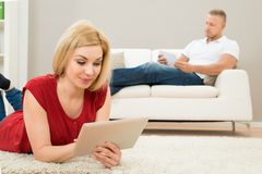 Woman using digital tablet with a man on sofa Royalty Free Stock Image