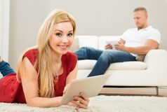Woman Using Digital Tablet With A Man On Sofa Stock Image