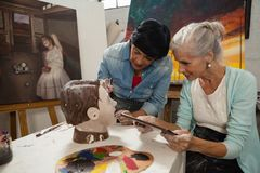 Woman using digital tablet while painting a sculptor. In drawing class Royalty Free Stock Photo