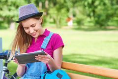 Woman using digital tablet at the park. Gorgeous young hipster woman smiling while surfing internet on her digital tablet copyspace education online shopping stock photo