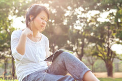 Woman using digital tablet in park Stock Image