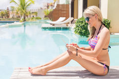 Woman using digital tablet by the pool Royalty Free Stock Image