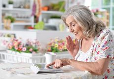 Woman  using digital tablet. Portrait of a happy senior woman using digital tablet Stock Image