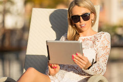 Woman using digital tablet while sitting in deck chair Royalty Free Stock Image