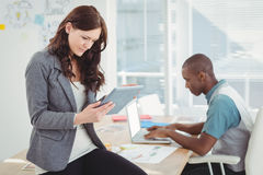 Woman using digital tablet while sitting on desk with man working. Woman using digital tablet while sitting on desk with men working in office Royalty Free Stock Photos