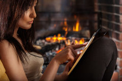 Woman using digital tablet sitting by fireplace Royalty Free Stock Image