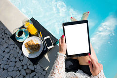 Woman using digital tablet while sitting in swimming pool royalty free stock photo