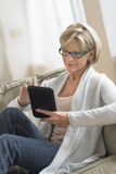 Woman Using Digital Tablet On Sofa stock photo