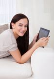 Woman using digital tablet on sofa Royalty Free Stock Images